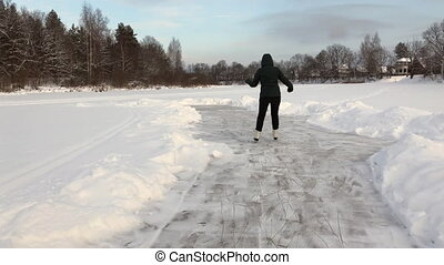 Young woman ice skating frozen lake forrest nature -...