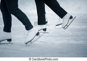 Young woman ice skating outdoors on a pond on a freezing winter day - detail of the legs (color toned image)