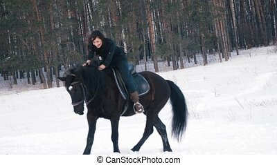 Young woman ider walking a black horse through the deep...