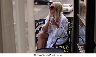 young woman in a bathrobe and sunglasses drinks coffee on the balcony in the morning