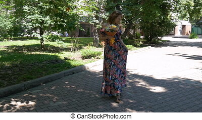 Young woman in a beautiful dress walking in the park, with a bouquet of flowers.