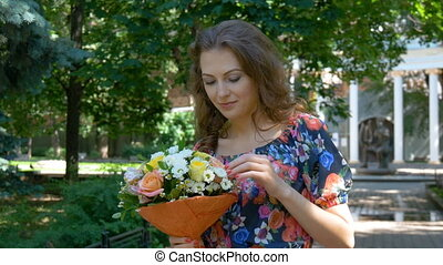 Young woman in a beautiful dress walking in the park, with a bouquet of flowers. close-up Beautiful smile.