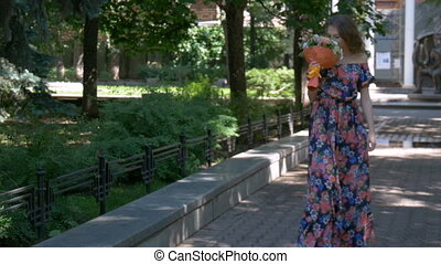 Young woman in a beautiful dress walking in the park, with a bouquet of flowers. close-up