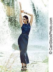 Young woman in a beautiful fashion dress posing outdoors