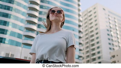 Young woman in a big city in summer looks in different...