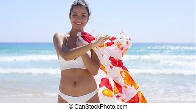 Young woman in a bikini standing on a beach holding a...