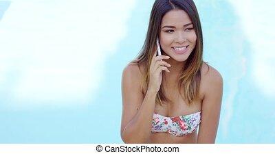 Young woman in a bikini talking on a mobile