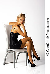 young woman in a black dress posing sitting on a chair