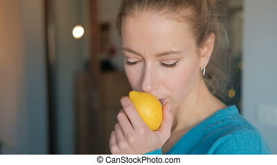 Young woman in a blue blouse inhales the aroma of fresh lemon.