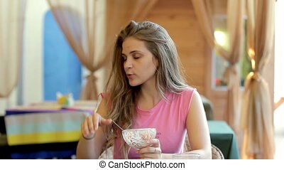 Young woman in a cafe eating ice cream. Talking to a girlfriend