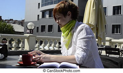 young woman in a cafe writing