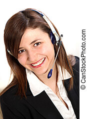 Young Woman in a call center. She wears a headset and smiles toward the camera