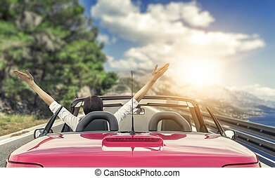 Young woman in a car on the road to the sea against a backdrop of beautiful mountains on a sunny day.
