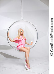 Young woman in a chair on a white background. Geometry. Blonde in a pink dress in a plastic round chair