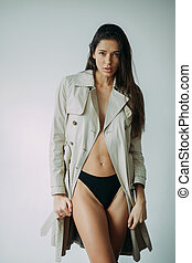 Young woman in a coat and bikini posing in the studio.