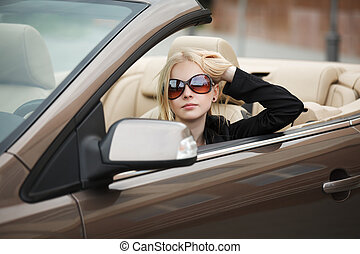 Young woman in a convertible car