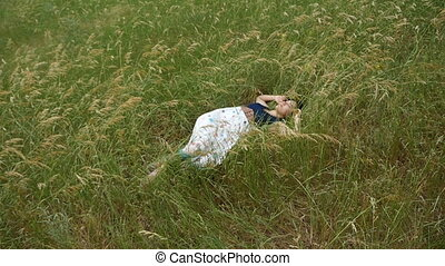 Young woman in a country dress sleeps among hign grass on a sunny day in slo-mo