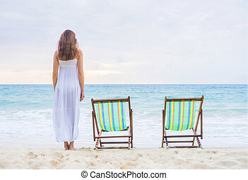 Young woman in a dress on the beach