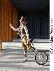 Young woman in a fantasy clothes with unicycle outdoors