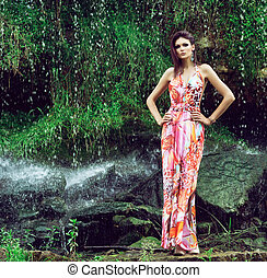 Young woman in a fashion dress posing next to a waterafll