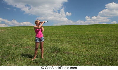 Young woman in a field look into sp