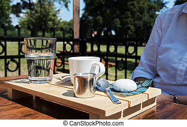 Young woman in a garden restaurant with a glass of water, coffee and milk
