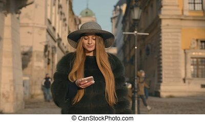 Young woman in a gray hat and long hair communicates via smartphone