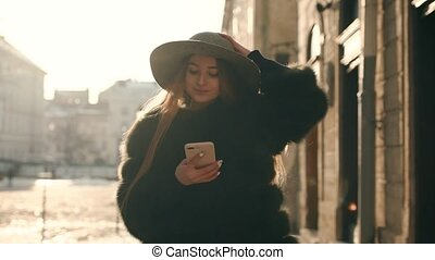 Young woman in a gray hat and long hair writes sms via smartphone