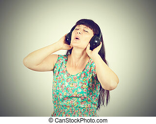 Young woman in a green dress listening to music with headphones