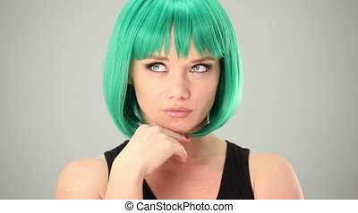 Young woman in a green wig having a bright idea