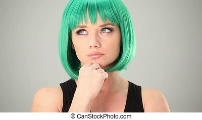 Young woman in a green wig with a thoughtful look