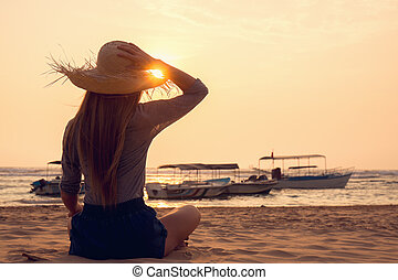 woman in a hat looking at the sunset