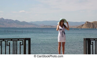 Young woman in a hat on the embankment against the sea.