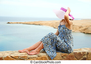 woman in a hat on the seashore