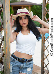 Young woman in a hat posing on the street.