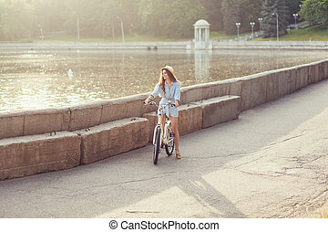 woman in a hat with a bike in the park