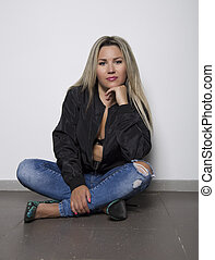 Young woman in a jeans sitting on the floor near white wall