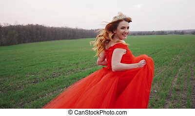 young woman in a luxurious red dress runs along the green field and smiles