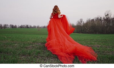 young woman in a luxurious red dress runs along the green grass