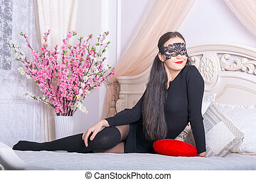 Young woman in a mask on the bed