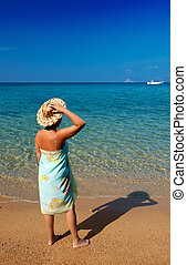Young woman in a pareo and straw hat, standing on a Mediterranean sandy beach and looking into the blue sea