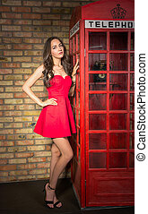 Young woman in a red dress near the old phone booth