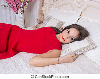 Young woman in a red dress on the bed