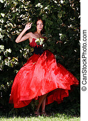 Young woman in a red gothic dress