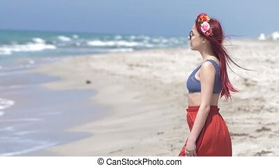 young woman in a red skirt and blue top with red hair flying in the wind and a floral wreath in her hair against the backdrop of the stormy sea