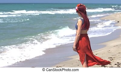 young woman in a red skirt and blue top with red hair flying in the wind looks at the stormy sea