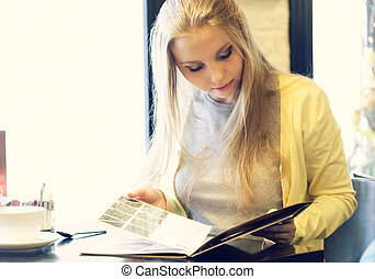 Young woman in a restaurant reading the menu