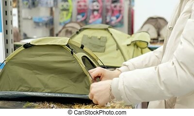 young woman in a specialty store for the tourism picks camping tent 4k