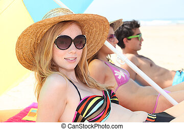 Young woman in a straw hat sunbathing on the beach with friends