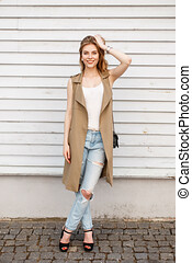Young woman in a stylish summer vest in a white T-shirt in fashionable blue ripped jeans in black shoes with a leather handbag posing outdoors against a white wooden vintage wall. Lovely girl smiling
